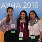 three smiling women in front of APHA 2016 logo