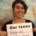 smiling woman with Our taxes sign