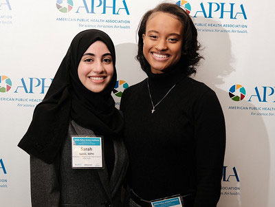 two women smiling in front of APHA logo backdrop