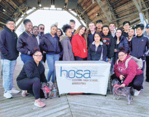 smiling people gathered behind 'hosa' banner