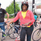 smiling woman standing next to bike