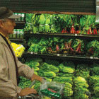 man pushing grocery cart in produce aisle